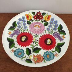 A beautiful hand painted porcelain plate made in Kalocsa Hungary.  Its floral design is beautiful and colorful!  Rimmed in gold, it has two holes in the
