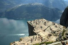 """Preikestolen or Prekestolen, also known by the English translations of Preacher's Pulpit or Pulpit Rock, and by the old local name Hyvlatonnå (""""the carpenter-plane's blade""""), is a massive cliff 604 metres (1982 feet) above Lysefjorden, opposite the Kjerag plateau, in Forsand, Ryfylke, Norway. The top of the cliff is approximately 25 by 25 metres (82 by 82 feet) square, almost flat, and is a famous tourist attraction in Norway."""