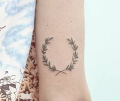 Hand poked laurel wreath tattoo on the back of the right arm.
