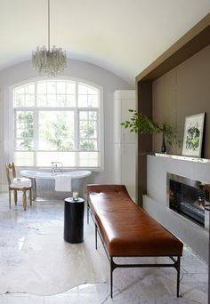 In the expanded master bathroom, Beckstedt designed a contemporary walnut, leather, and limestone fireplace with polished nickel trim accents. The chandelier is a vintage Italian fixture from Las Venus, and the polished nickel tub is from Urban Archaeology.