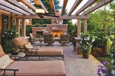 A rustic wood pergola stretches protectively over two striped lounge chairs creating a quiet retreat out of this home's beautiful patio. A fireplace at one end cozies up cool nights and afternoons, and a ceiling fan attached to the wood beams makes a welcome breeze when temperatures climb.