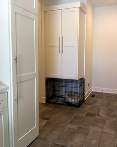 A creative built-in dog kennel in this mudroom.  White cabinets, dark tile floor.