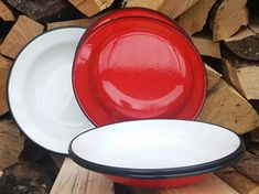 Enamel plates with red underside and cream top and black rim around the edge. These enamel plates are called flat, they are deep and diameter.