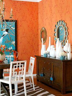 This Mandarin-inspired dining room exudes bold style in colors, furnishings, and accents. Wallpaper offers depth with its layers of orange tones in a branch print. Vibrant Asian-theme artwork is a standout with its azure background. White Chippendale-style chairs and a collection of white vases work with the Far East theme and play to the whites in the artwork.