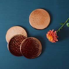 Simple but oh so stylish copper coasters.What an easy way to bring the copper trend to your home décor and these copper effect coasters make a fab present as they come as a set of four in a stylish black gift box. The hand beaten, dimpled finish adds a wonderful texture to the design. These coasters have a rubber backing to protect your surfaces.Aluminium with a copper dye coating. Wipe clean only.D10cm
