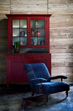 A handcrafted chair upholstered in vintage indigo textiles backed by an antique cupboard in bold red.