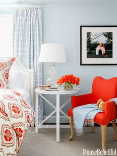 Master Bedroom.  Orange chair and bedding with orange accents.  Round white side table.
