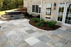 Go a step beyond the plain old concrete or wooden patio and use natural stone.  A combination of large and small multi-color natural cleft slate tile from Carved Stone Creations creates a very unique patio for this home.  The steps for the hot tub also match the patio. available on our online store. #stonetile.  T stripes, M t gray