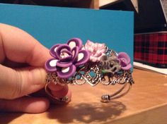 Silver filigree bangle bracelet topped with polymer clay flowers, centered with clear gems