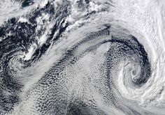 """NASA Terra Satellites Moderate Resolution Imaging Spectroradiometer - April 2009 - """"Cyclones"""" over the South Atlantic Ocean - Cyclones like these are often created by low-pressure systems over cold, open water; the spot of green in the upper left is water just off the southern tip of Africa."""