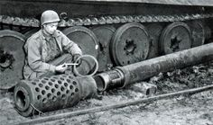 US soldier watching muzzle brake and barrel of 17cm Kanone - armament from prototype of self-propelled gun.