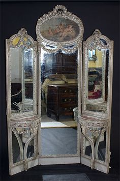 French, Louis XVI style tri-fold, full-length mirror: Each side panel with attached console table, having hinged top. Center mirrored panel beneath trumeau depicting cherubs at play. 19th century.
