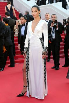 One of the most glamorous red carpets of the year, Cannes Film Festival, is officially here. Adriana Lima wears a white and black high-slit gown and high ponytail. See all the best red carpet fashion from Cannes here: