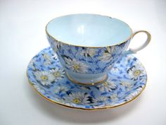 Beautiful tea cup and saucer from Shelley, Daisies chintz pattern. The interior of the tea cup is light blue. The rims are highlited with gold. C. 1954 - 1960 Cup Measures: 2 3/8 high & Saucer Measures 5 1/2 diameter Excellent conditon, no chips, no cracks, no crazing and both