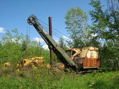 Woods gradually surround old road-building equipment. Bucyrus Erie, Winning The Lottery, Heavy Equipment, Utility Pole, Woods, Cable, Iron, Construction, Building