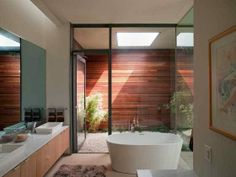 Ultra-slick modern bathroom in Texas has an oval stand alone tub, wood cabinets, dual sinks, framed art work, a wall of glass that opens to the wood lined outdoor shower.