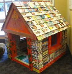 Novel idea of what to do with worn books.  Miniature house made out of stacked books, with books for shingles on the roof - Iowa City Public Library!