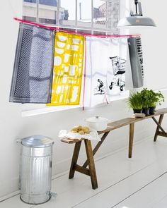 Don't have a curtain? It's okay, hang some pretty tea towels next to your kitchen window. And add a nice wooden bench with some herbs pots.