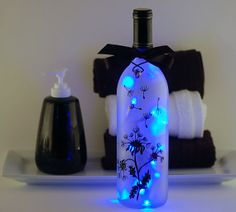 Wine bottle lamp hand painted with black dandelions on a frosted bottle filled with blue lights