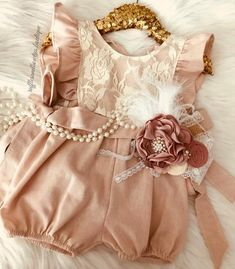 Baby Girls Elizabeth Dusty Pink Lace Ruffled Cap Sleeve Baby Romper/Jumper  Our sweet Elizabeth romper features soft dusty rose colouring with a delicate lace overlay on the upper bodice. Adorned with sweet flutter cap sleeves and a tie back featuring full upper bodice lace coverage, with bow ties, this dainty romper is much like a favorite heirloom waiting to be passed down.