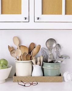 Martha likes to keep metal and wooden utensils separated. In this case, they are in different pots, within a woven tray.