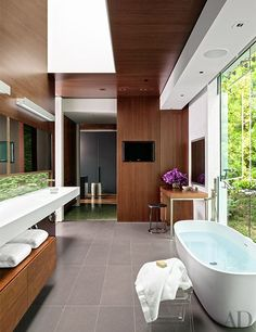 Anchored by an Agape tub, the master bath has an integrated sink and countertop by Antonio Lupi.