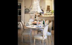 Höggustavianska stolar i originalfärg med gråvitrandig klädsel inramar ett modernt bord med stålben. Lampa från Kartell.