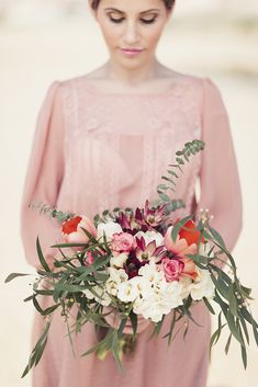 Blush long-sleeved bridesmaid dress with soft blush, neutrals and deep reds and some neutral greens for the bouquet. Photo by André Teixeira, Brancoprata.