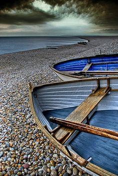 Row boats on beach rocks.