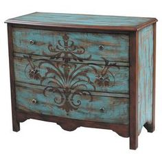 "Three-drawer chest in antiqued teal with a stenciled floral motif.  Product: ChestConstruction Material: WoodColor: Teal and brownFeatures: Three drawersDimensions: 35"" H x 38"" W x 19"" D"