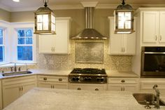 White and gray kitchen with Avente Tile's Zebra B pattern cement tile and tin ceiling tile for the backsplash.