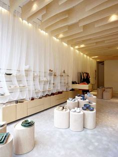 Japanse Winkeltje by Nezu Aymo Architects: Loops of white mesh made of paper yarn soaked in rice water surround the wooden shelves.