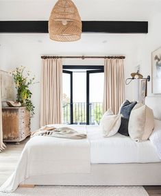 Contemporary bedroom with a white and off white colour scheme.  Pops of pale coral in the curtains. Design by Janette Mallory Interiors