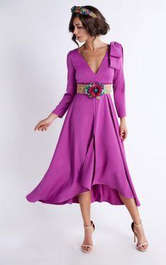 Vestido buganvilla corto con falda de vuelo y lazada en el hombro. Cinturón de flores y pedrería incluido. Escote en pico y mangas 3/4. Ligera abertura en la parte frontal del vestido.