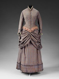 1883 - A short puffed overskirt creates elaborate draped effects on this fashionable walking costume. Draperies were very popular during the 1880s, and pleats, poufs, gathers, panniers, swags and asymmetrical effects produced great fullness around the hips, making the waist appear very slende