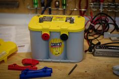 Ready To Go - A new looking #car #battery sits on a work bench, ready for installation. This clean and organized workspace looks like the perfect place to check your battery over before making the switch