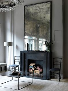 Moody living space with a black fireplace and a large mirror