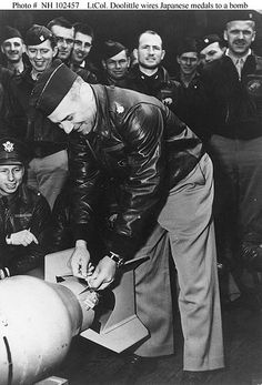 """Lt. Col. Doolittle wires a Japanese medal to a bomb, for """"return"""" to Japan"""