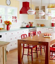 sunny paint color | mint green countertops | farm-style kitchen table | built-in paper towel roll  | homemade cafe curtains | schoolhouse lighting - CountryLiving.com