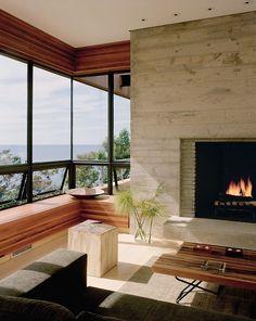 O Frio Chegou, Acendam as Lareiras | Decorando com Classe. Projeto Robert Yong Archtects com lareira de concreto aparente. Sofá preto e banco em madeira teca com vista para o mar.