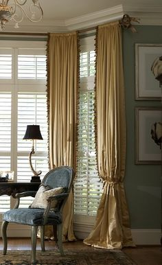 Classic rid pocket drapery with tassel fringe on decorative hardware over shutters Bay window
