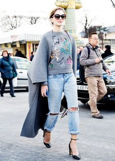 Gray graphic sweatshirt worn underneath a gray oversized coat, ripped jeans and black ankle strap heels
