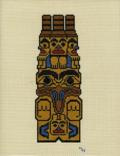 Totem Pole - Raven With Three Watchers - Haida.  I cross stitched this on vinyl-weave 14 count cross stitch fabric for a 3 ring binder cover.