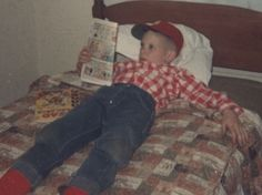 Comic book kid (me) on the bed. Nice red socks, my Minor baseball cap, and a checked red shirt at 7 years old. (About 1963)Looks like I'm reading a Dennis-The-Menace comic (my favorite) and there's a Sad Sack comic on the bed. Mother said that they could hear my loud laughing all over the house when I got a couple of new comics. I still have my huge entire comic collection to this day. (Dave Brock photo)