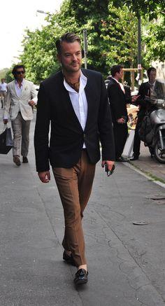 Shop this look on Lookastic:  https://lookastic.com/men/looks/blazer-long-sleeve-shirt-dress-pants-tassel-loafers-scarf/12175  — Brown Print Scarf  — White Long Sleeve Shirt  — Black Blazer  — Brown Dress Pants  — Black Leather Tassel Loafers