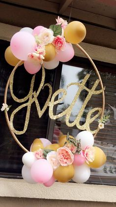 Spray painted a hula hoop gold & decorated it with balloons & flowers. Made name with cardboard, spray painted & topped with glitter.