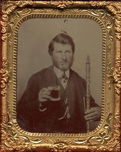 Musician with Flute and Mug, 1/9 plate Tintype of a man who is not afraid to drink a beer and play his instrument.
