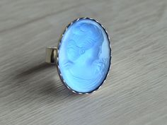 This handmade sterling silver ring has been set with a shimmering blue cameo. The back is reflective so it really catches the light in a beautfiul way. It measures 18 x oval and the edge .