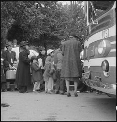 Hayward, California. Farm families of Japanese ancestry are being checked into the evacuation buses which are enroute to the Assembly center. Their identification tags and numbers are inspected before entering the bus by a member of the Wartime Civil Control Administration Control Station staff. Over 400 persons were evacuated from this district on this date. Dorothea Lange photo