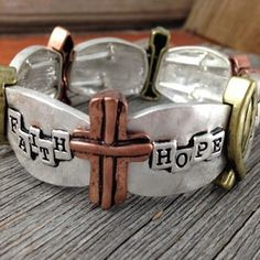 """I love the way this bracelet looks like it's a cuff but it stretches to easily fit over your hand.  The antiqued silver panels each say """"Faith"""", """"Hope"""", or """"Love"""". The cross, heart, and fish symbols are done in antiqued brass and copper colored metals.  Visit our new online shop for more Scripture based jewelry!"""